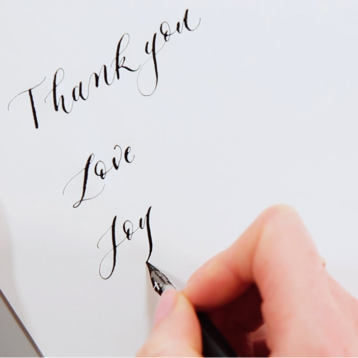 The words Thank you, Love and joy written in calligraphy
