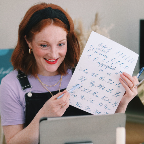 Lydia Holding up a modern calligraphy alphabet and teaching an online calligraphy class