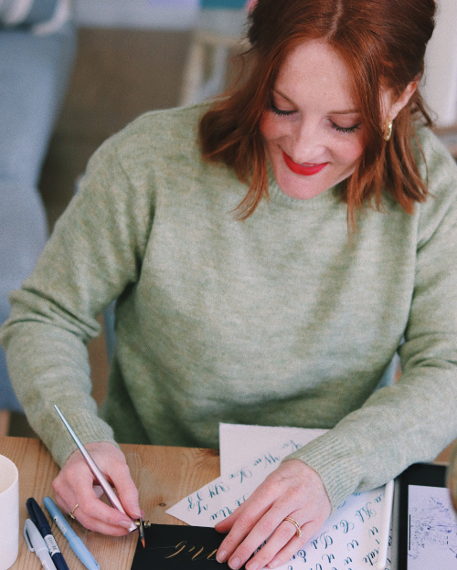 Lydia writing calligraphy at her desk