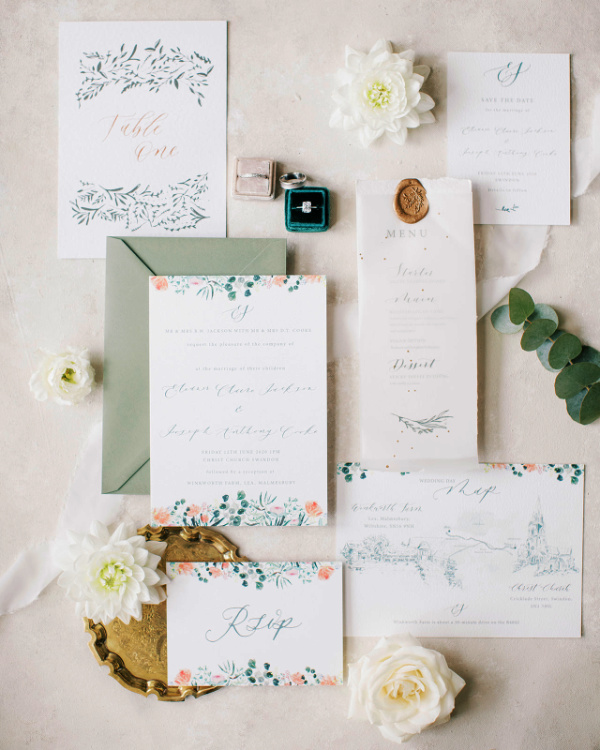 Hand illustrated wedding stationery suite flat lay, surrounded by flowers and leaf detail